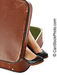 Female feet in suitcase