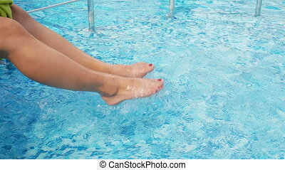 Female feet in the pool move water, rest by the pool