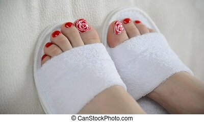 Female feet in white slippers on couch - Female feet in...