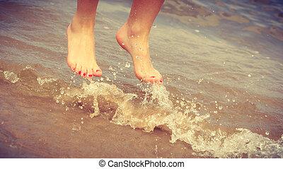 Female feet jump on beach.