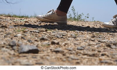Female feet of hiker goes on the top of cliff in mountains. Legs of girl in sneakers steps on the rocky terrain. Woman tourist hikes on the pathway at hill. Concept of summer adventures. Low view.