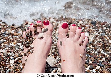 Female feet on a background of sea water