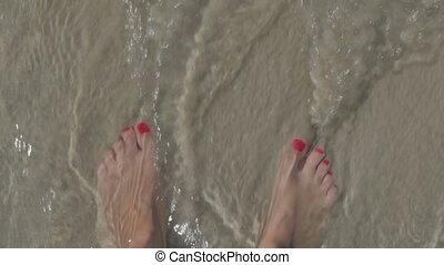 Female feet on a sandy beach and sea waves.