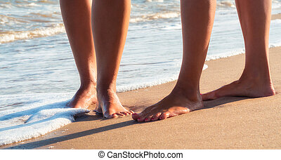 female feet on a sandy beach in the waves of the surf of the sea in summer close up