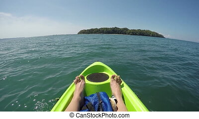 female feet relaxing on kayak in pacific ocean point of view...