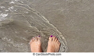 Female feet sea shore on holiday, woman relaxing on beach