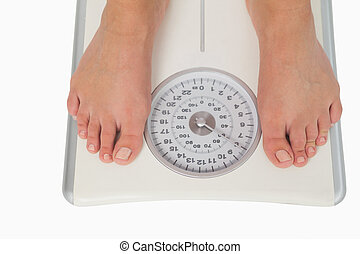 Female feet standing on a scales