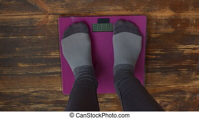 Female feet standing on weight scales