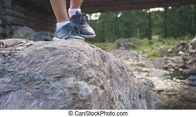 Female feet traveler stepping on the stones at mountain landscape in beautiful sunny summer day in slow motion. 1920x1080