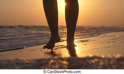 Female feet walking on beach barefoot at golden sunset in slow motion. Close up. 1920x1080