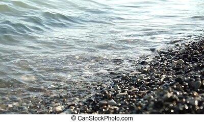 Female feet walking on the peeble beach