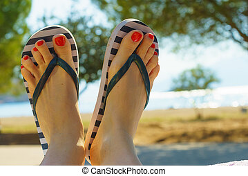 Female feet wearing flip flops having red nails