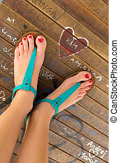 Graphical image of beautiful healthy female feet with red nailpolish applied on the nails wearing turquoise summer leather sandals standing by heart shaped graffiti drawn on a wooden surface.