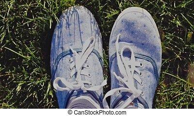 Female feet wears sneakers in blue jeans color sports shoes...