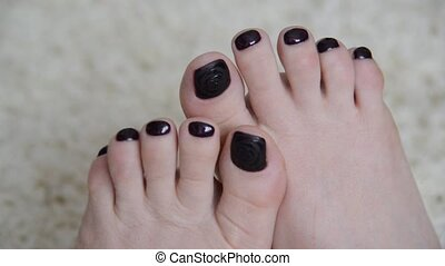 Female feet with a dark paint on nails