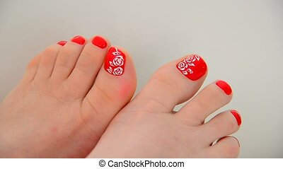 Female feet with a red nail polish and floral pattern