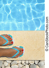 Female feet with flip flops by the pool