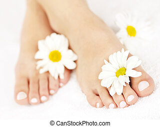 Soft female feet with pedicure and flowers close up