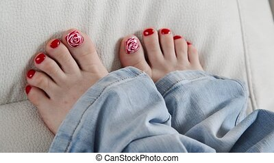 Female feet with red lacquer on nails on couch