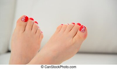 Female feet with red nail polish and floral pattern