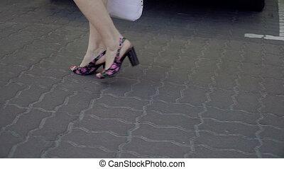 Female feet. Women's feet go on the asphalt on their heels