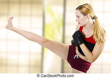 Female fighter kicking leg high side