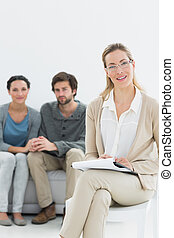 Female financial adviser with young couple in background -...