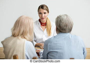 Female financial advisor talking consulting senior aged couple a