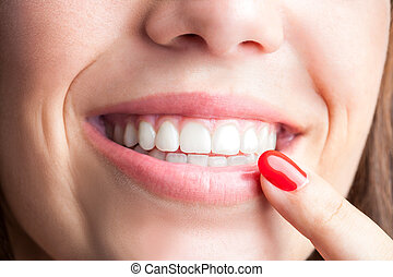 Female finger pointing at teeth