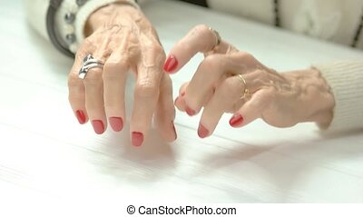 Female fingers imitating play on piano. Elderly woman...
