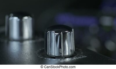Close-up of female fingers with french manicure turning shiny silver metal audio interface knob.