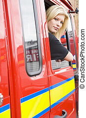 Female firefighter sitting in the cab of a fire engine