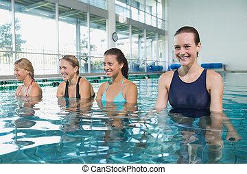 Female fitness class doing aqua aerobics in swimming pool at...
