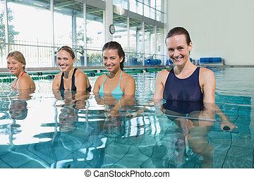 Female fitness class doing aqua aerobics