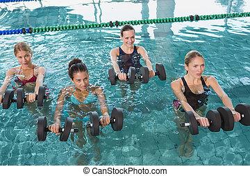 Female fitness class doing aqua aerobics with foam dumbbells