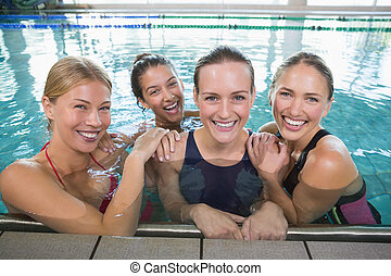 Female fitness class smiling at camera in swimming pool at...