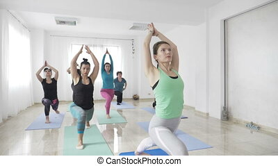Female fitness instructor teaching warrior pose to middle...