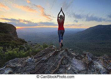 Female fitness stretch to the sky mountain top valley scene