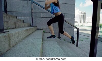 Female fitness trainer working out on stairs, preparing for training - stretching and doing squats