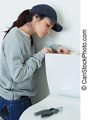 female fixing a toilet