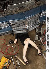 female fixing her car