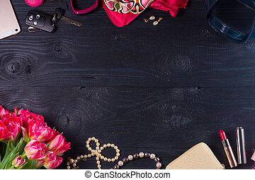 female flat lay styled scene borders - fresh flowers and accessories on black wooden background