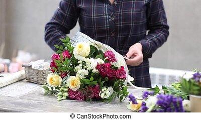 Female florist arranging flowers in flower shop. Florist packing bouquet with bouquet cover paper