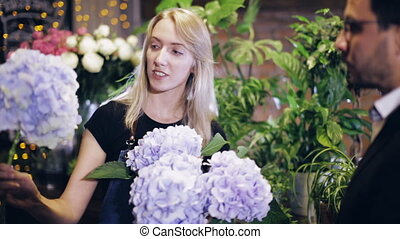female florist consults a customer in a flower shop - female...