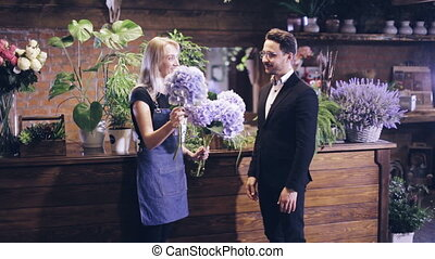 female florist consults a customer in a flower shop -...