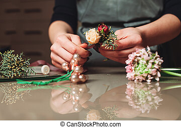 Female florist creating bouquet decoration closeup