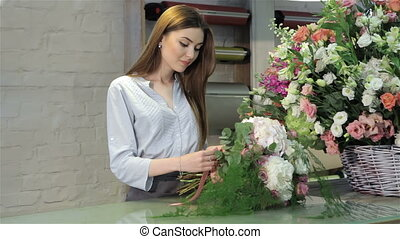 Female florist demonstrate a bouquet of white flowers at flower shop