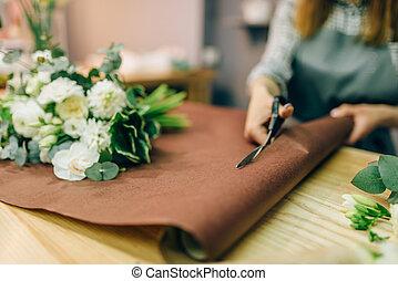 Female florist hands cuts decoration with scissors