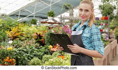 Female florist holds black tablet at the garden centre