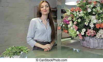 Female florist leans on her working desk